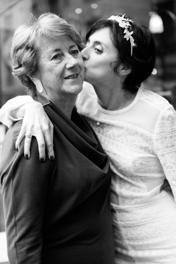 Bride kissing her mother in black and white