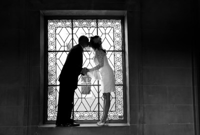 bride and groom kissing in front of window at City Hall
