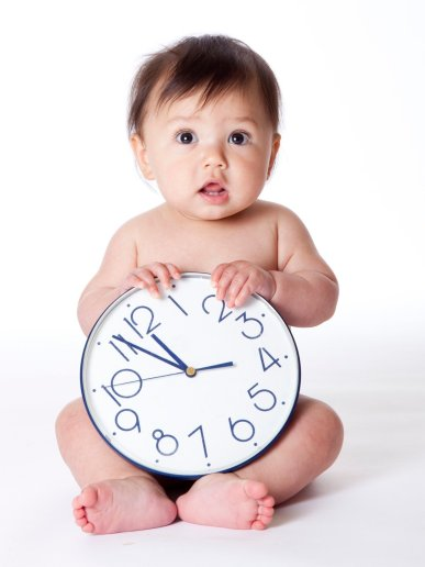 6 month old baby girl naked with clock in her lap