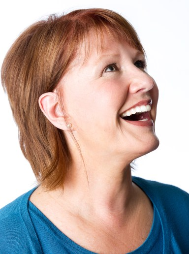 Portrait of woman with red hair in profile laughing
