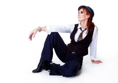 Female dancer dressed in male clothes sitting on floor