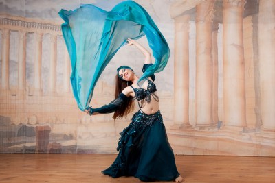 Female belly dancer with green scarf in the air