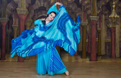 Female belly dancer with blue scarf