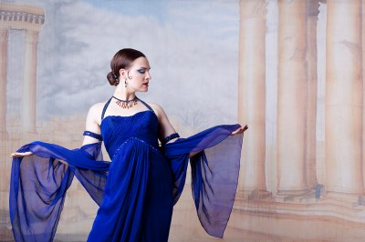 Woman wearing blue in profile with silk backdrop