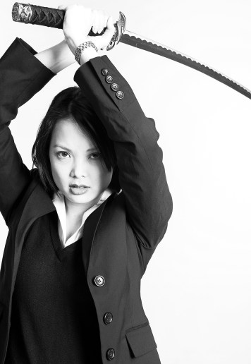 Black and white of woman carrying sword above her head