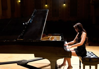Female pianist playing the piano on stage (from the back)