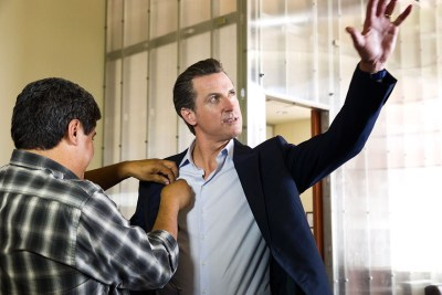 Gavin Newsom being mic'd with his arm up in the air
