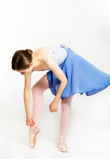 Female ballet dancer adjusting her the shoes