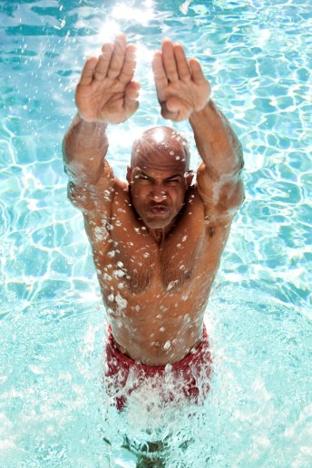 Bald headed man jumping out of swimming pool