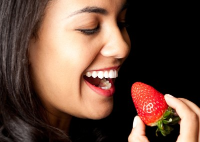 Shot of woman holding strawberry in hand with open mouth