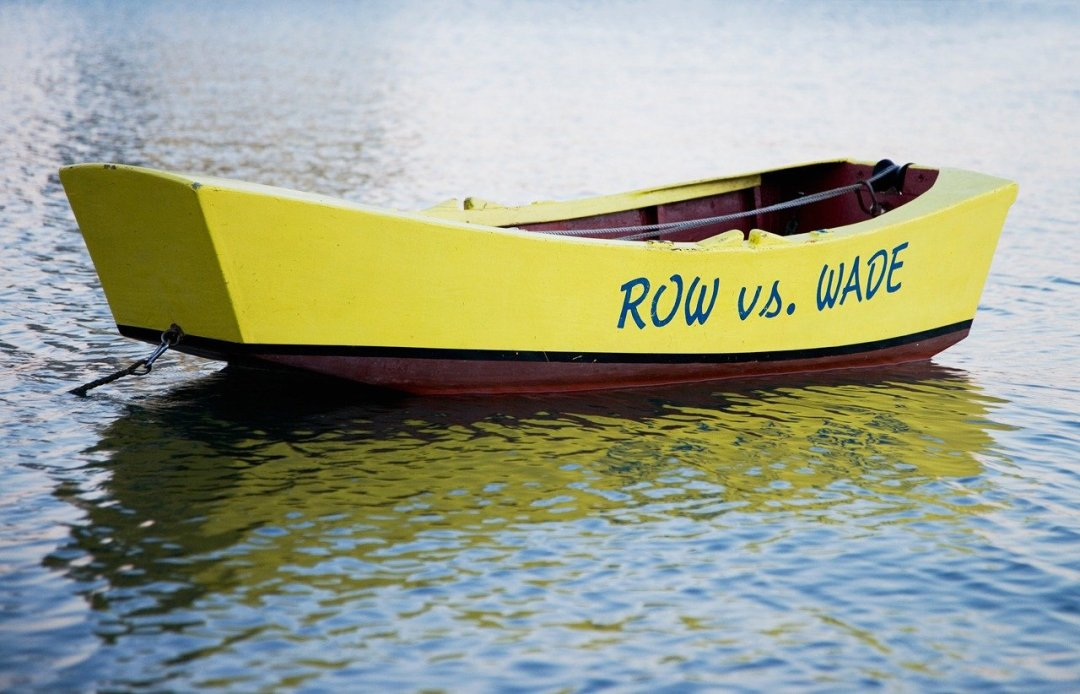 Wooden boat anchored with Row vs. Wade painted on it