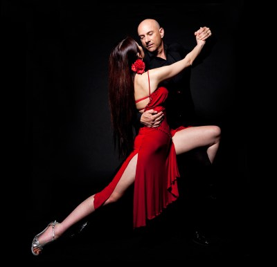 Couple doing tango on black backdrop