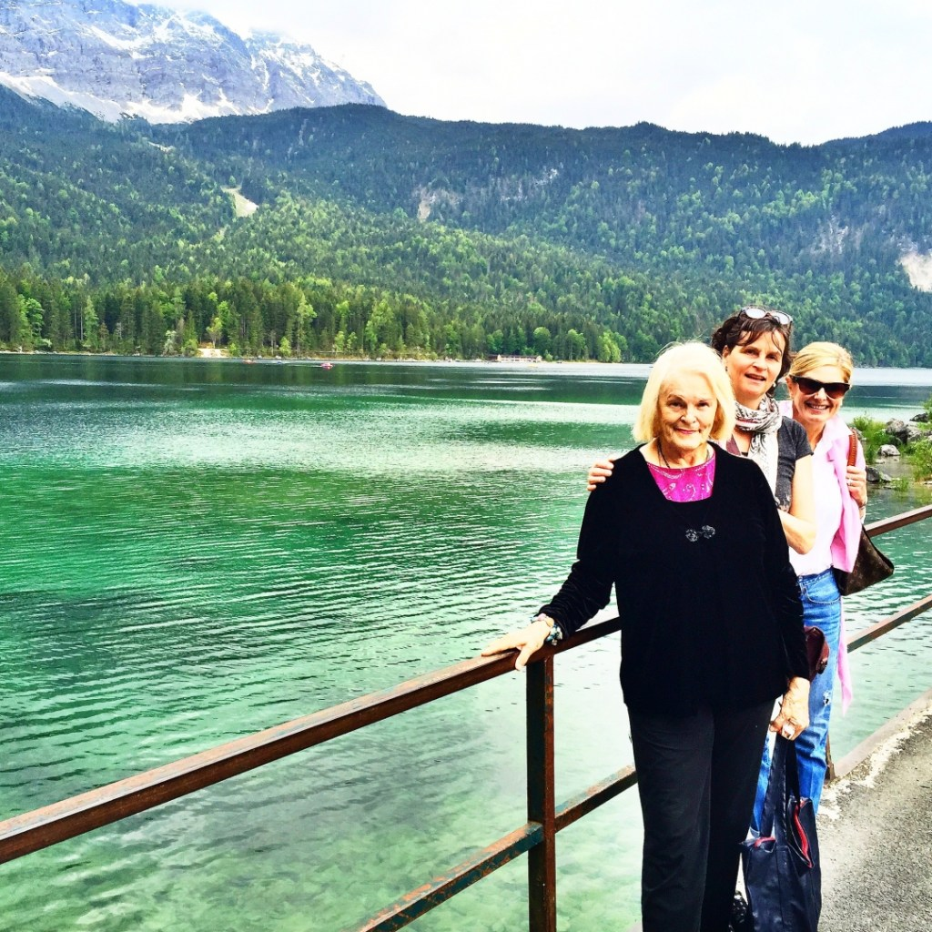 Tips on How to Move Forward After Losing a Parent by popular life and style blogger, Tanya Foster: image of three women standing next to a mountain lake in Oberammergau, Germany | by popular life and style blogger, Tanya Foster: image of