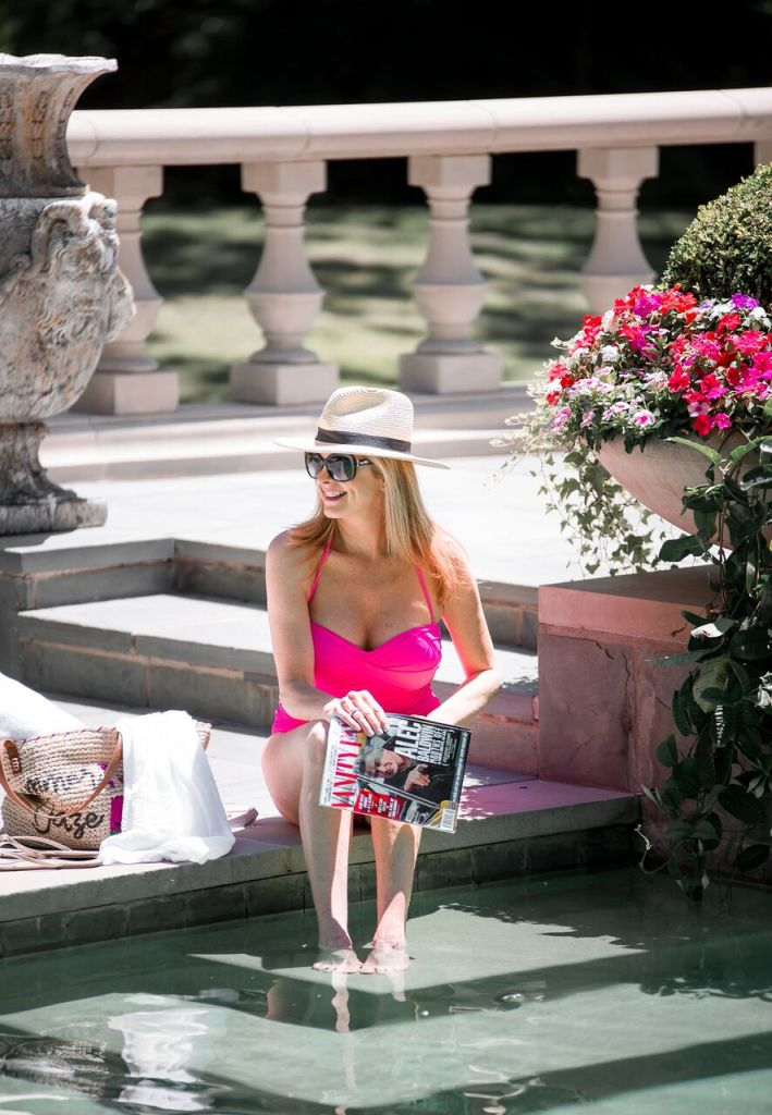 Hot pink one piece swimsuit with white cover up and beach bag from Nordstrom.