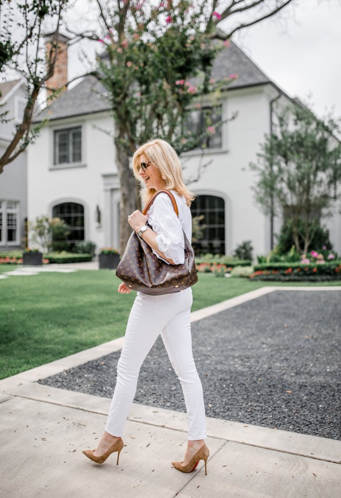 How to wear and protect your Christian Louboutin shoes. | 5 Best Designer Bags to Invest in and What's in my Bag by popular Dallas fashion blogger, Tanya Foster: image of a woman walking outside and holding a Louis Vuitton Artsy MM.