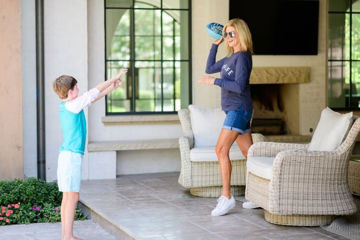 Tanya Foster in cabana life sweatshirt playing football with boy in cabana life swimsuit