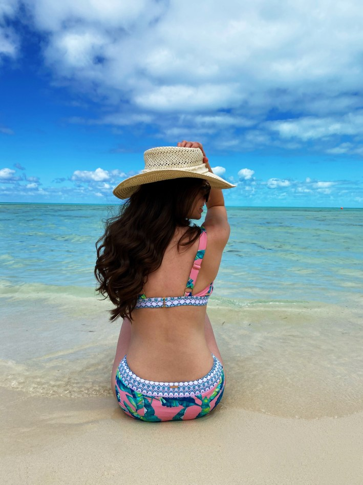 girl in cabana life bikini on the beach with a sun hat