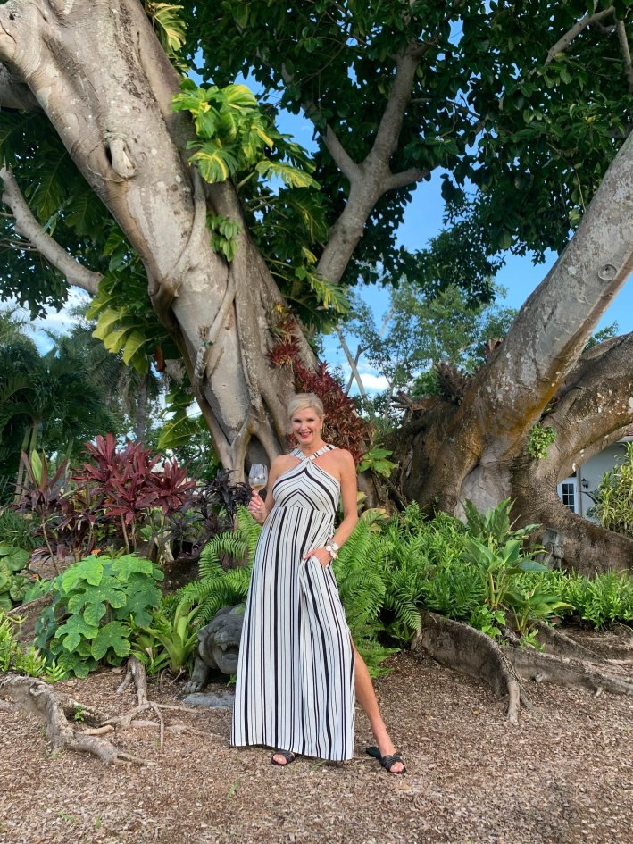 Soma influencer trip - Florida | Soma Influencer Brand Trip to Celebrate 15 Years! by popular Dallas influencer, Tanya Foster: image of a woman standing under a large tree, holding a glass of wine, and wearing a black and white striped maxi dress.