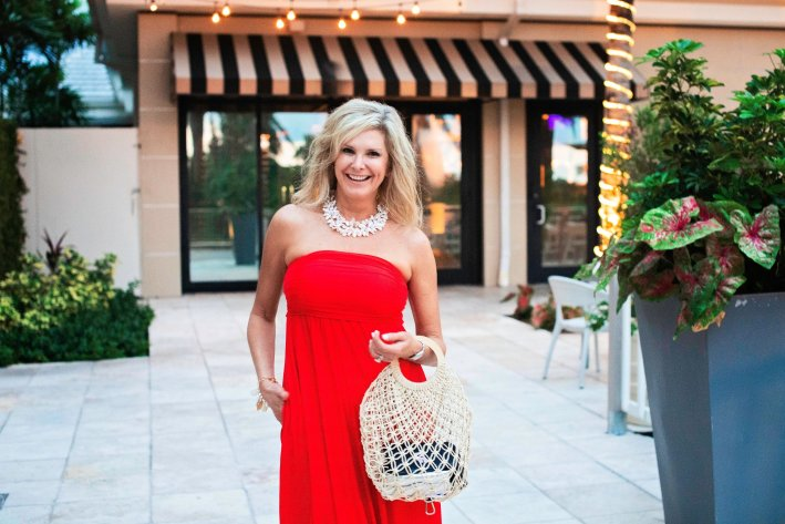 Soma Influencer Trip - Florida | Soma Influencer Brand Trip to Celebrate 15 Years! by popular Dallas influencer, Tanya Foster: image of a woman standing outside and wearing a red tube top maxi dress, metallic slide sandals, white statement necklace, and holding a mesh bag.