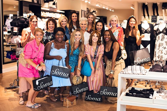Soma influencer trip - Florida | Soma Influencer Brand Trip to Celebrate 15 Years! by popular Dallas influencer, Tanya Foster: image of a group of women standing together in a Soma store and holding Soma shopping bags.
