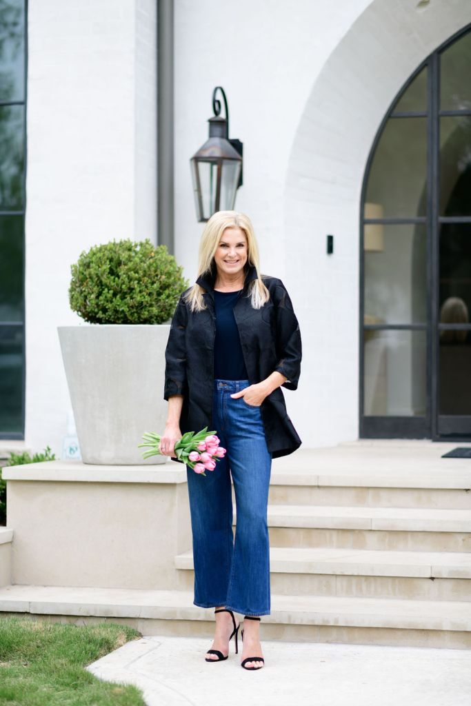 tanya foster in chico's wide leg jeans tank and organza jacket in black heels holding tulips