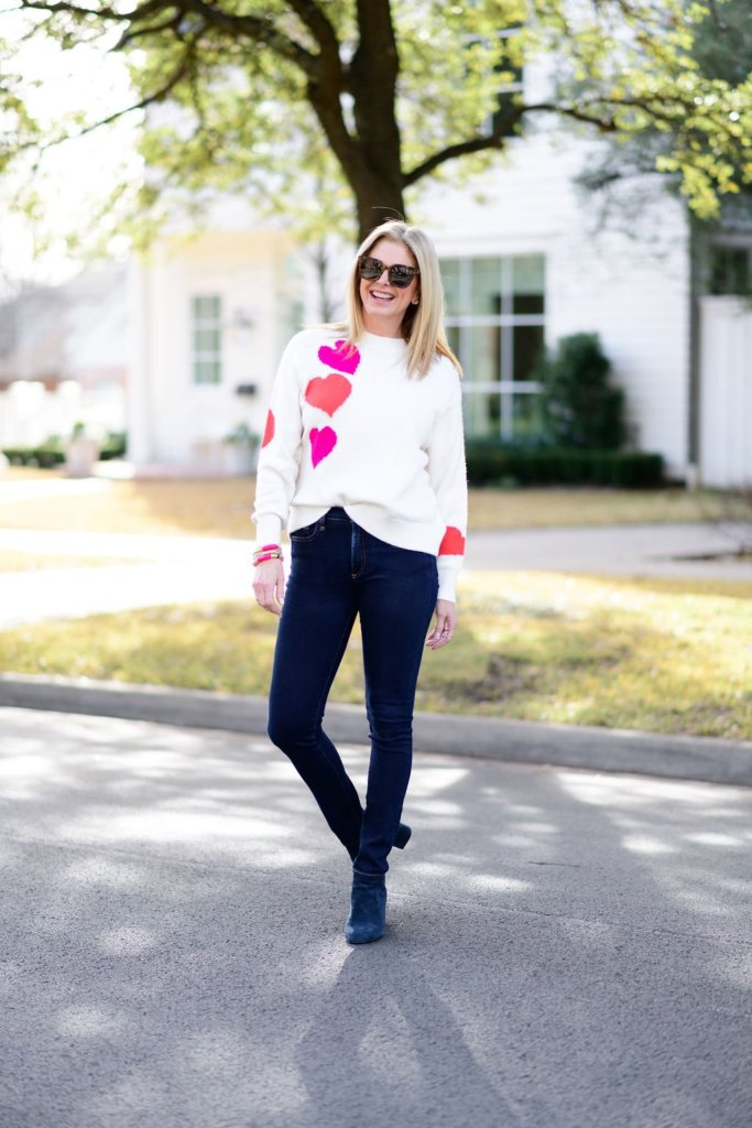 Tanya foster wearing loft heart sweater and veronica beard jeans with cecelia ny navy booties