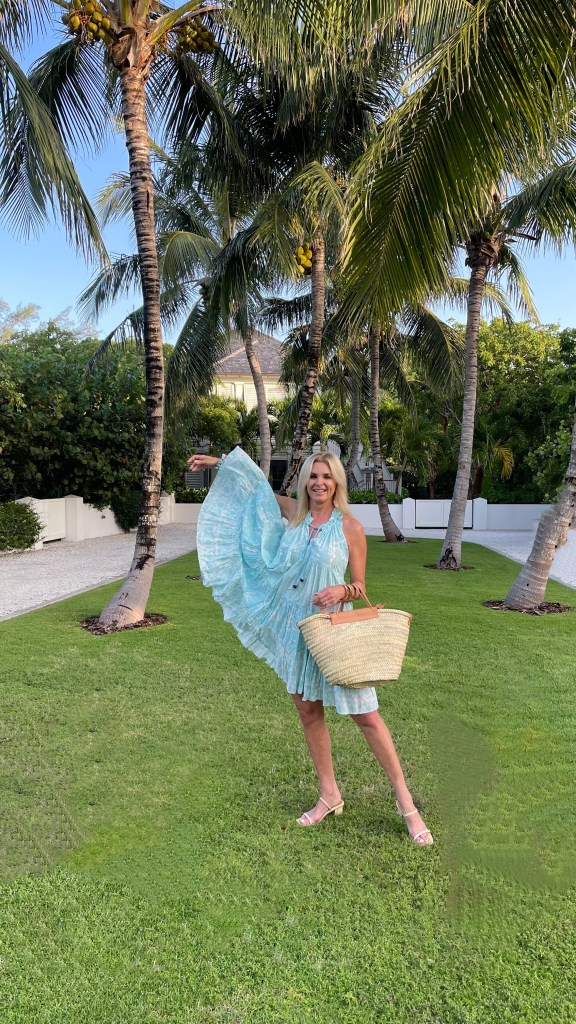 Tanya Foster wearing turquoise ro's garden dress dolce vita slide sandals and a mango straw tote bag