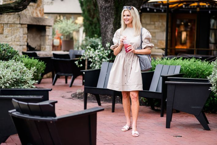 Tanya foster wearing beige dress with barrington tote and tuckernuck sunglasses with slide sandals