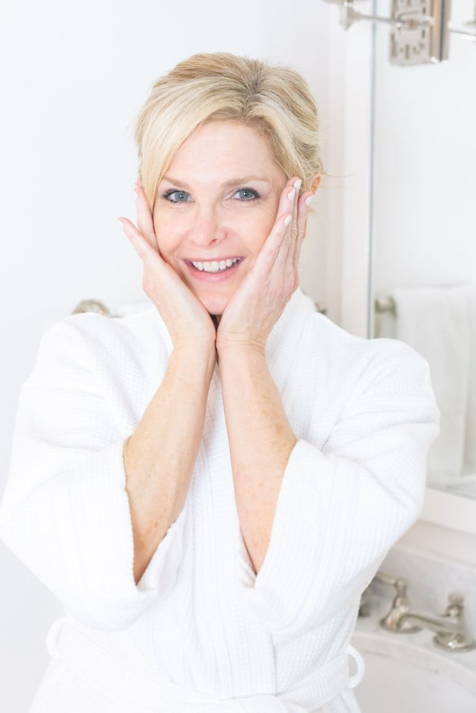 Mary Kay Naturally Product Launch | Introducing Mary Kay Naturally Collection by popular Dallas beauty blogger, Tanya Foster: image of a woman wearing a white bathrobe and pressing her hands on her cheeks.