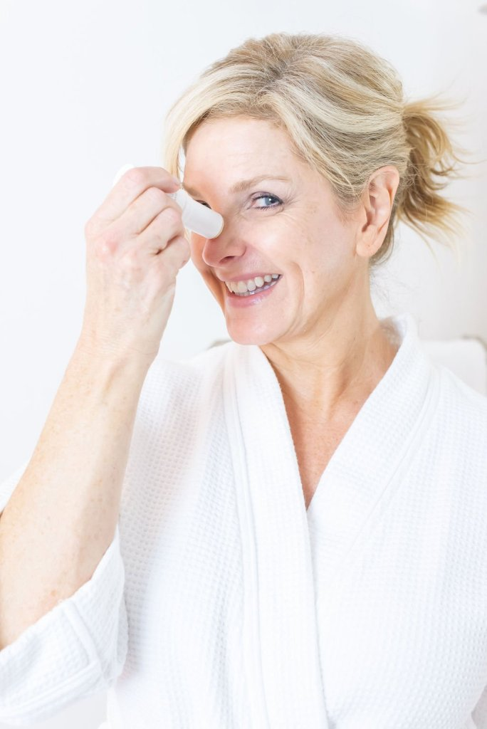 Mary Kay Naturally Product Launch | Introducing Mary Kay Naturally Collection by popular Dallas beauty blogger, Tanya Foster: image of a woman wearing a white bathrobe and rubbing a Mary Kay Naturally moisturizing stick to her face.