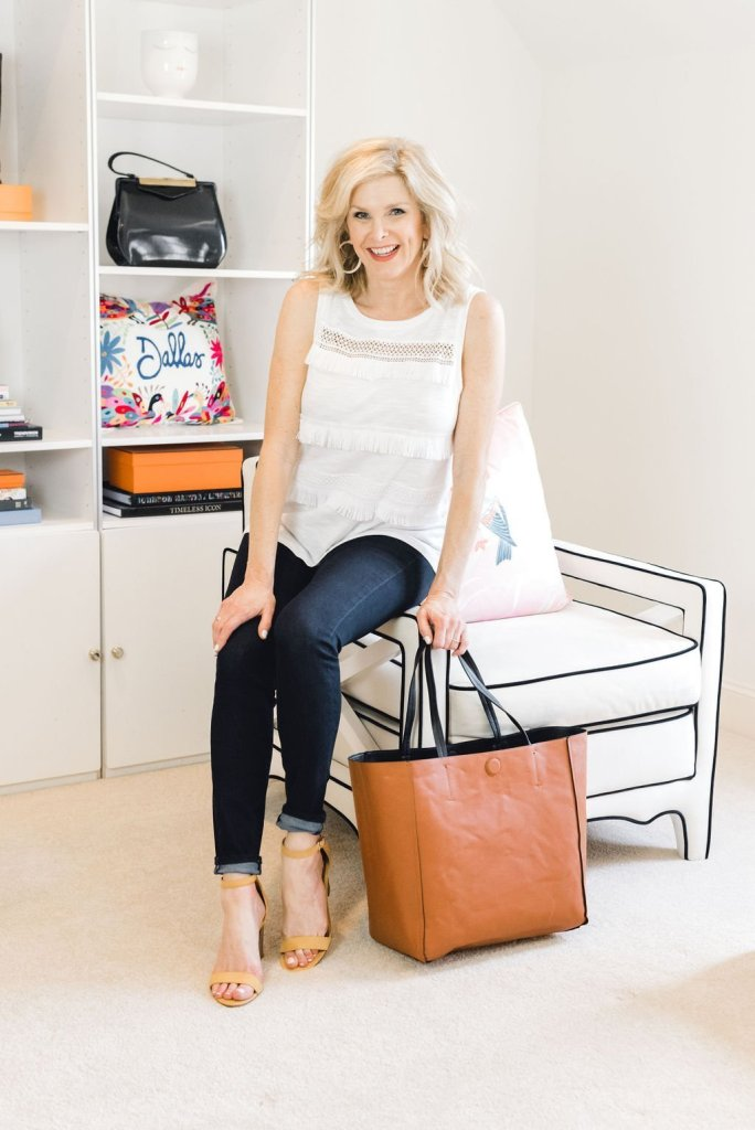 Skinny Jeans 3 Ways with JC Penney | Skinny Jeans 3 Ways by popular Dallas fashion blogger, Tanya Foster: image of a woman sitting on a white lounger chair and wearing a JCPenney a.n.a Skinny Jean, JCPenney Black Label by Evan-Picone Sleeveless Tie-Neck Blouse, JCPenney Collection Xiix Reversible Tote Bag, JCPenney Worthington Womens Beckwith Heeled Sandals, and JCPenney Gold Reflection 60mm Hoop Earrings.