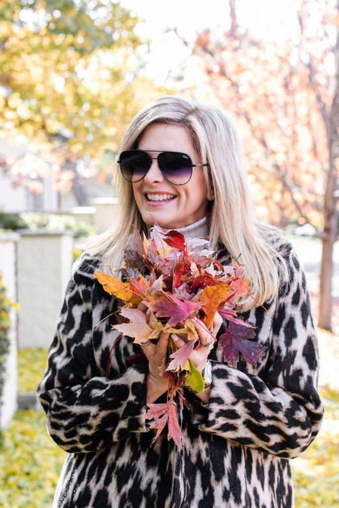 Tanya Foster holding leaves in her animal print coat