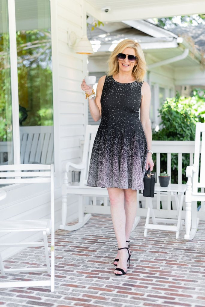Day to night dresses - Eliza J | Best Day to Night Dresses by popular Dallas fashion blogger, Tanya Foster: image of woman standing outside on a porch and wearing an Eliza J Ombré Dot Fit & Flare Sweater Dress and black Stuart Weitzman Nudistsong Ankle Strap Sandals.