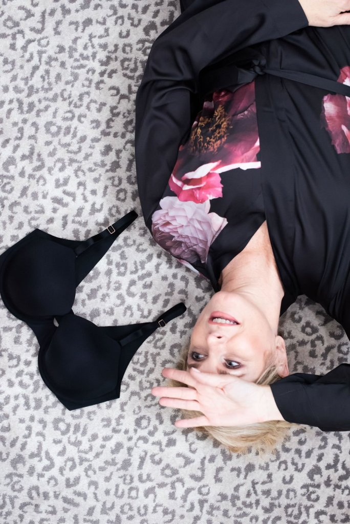 5 Tips for Bra Shopping by popular Dallas fashion blogger, Tanya Foster: image of a woman lying on the floor and looking at her black Soma Vanishing 360 bra.