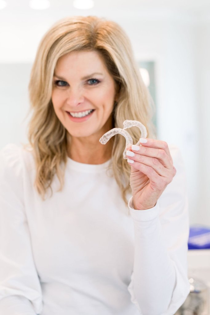 Tanya Foster holding aligners from Smile Direct Club
