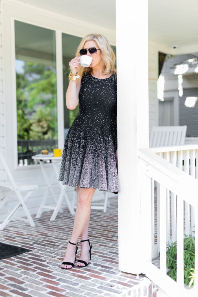 Day to night dresses - Eliza J | Day to night dresses - Eliza J | Best Day to Night Dresses by popular Dallas fashion blogger, Tanya Foster: image of woman standing outside on a porch and wearing an Eliza J Ombré Dot Fit & Flare Sweater Dress and black Stuart Weitzman Nudistsong Ankle Strap Sandals.