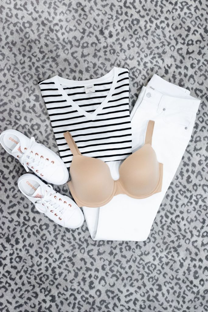 How to stop bra lines from showing with Soma Full Coverage Bra | Eliminate Bra Lines With a Soma Enbliss Bra by popular Dallas fashion blogger, Tanya Foster: image of a Soman Enbliss Bra lying on top of a striped shirt and white jeans.