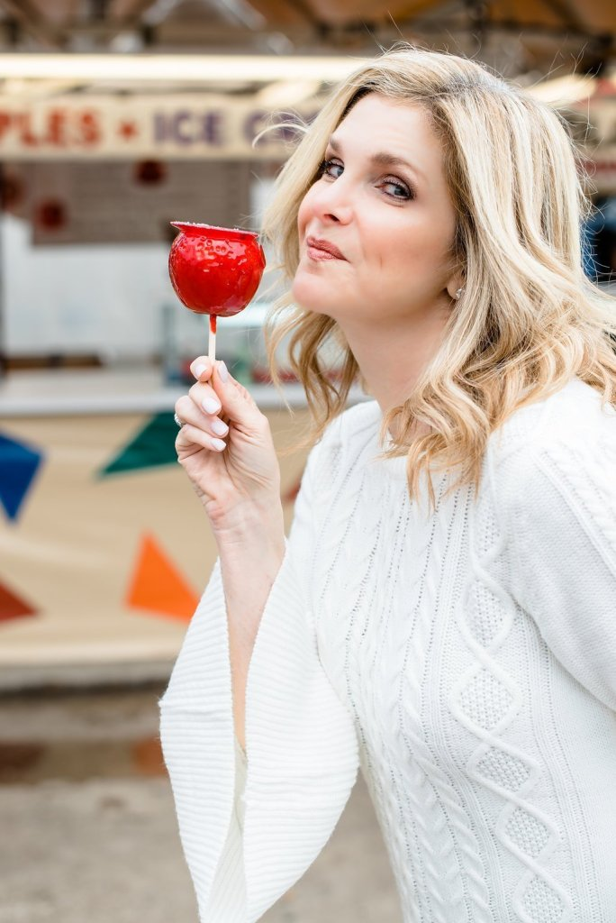 10 Things to do at the Texas State Fair! by popular Dallas blogger, Tanya Foster: image of a woman holding a candy apple at the Texas State Fair.