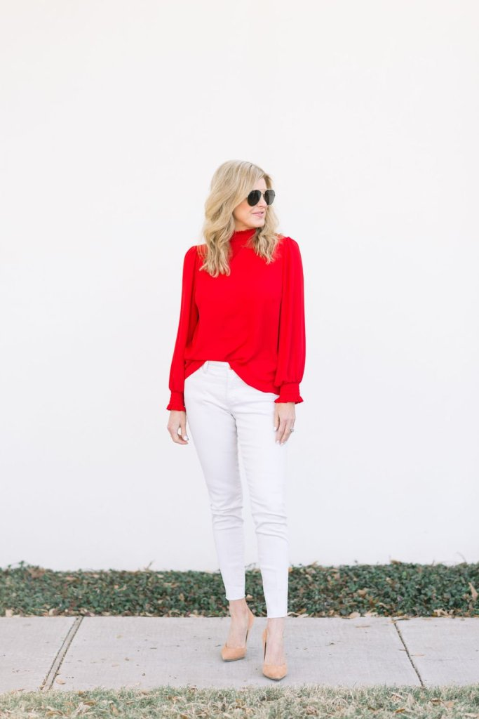 Tanya Foster standing on a sidewalk in red blouse and winter white jeans