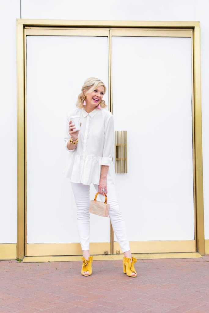 How to Wear Colored Shoes  featured by top US fashion blogger, Tanya Foster: image of a woman wearing Jimmy Choo yellow mules, Articles of Society white skinny jeans, love heart sunglasses, Julie Vos Valencia Bracelet, and and Edie Parker clutch