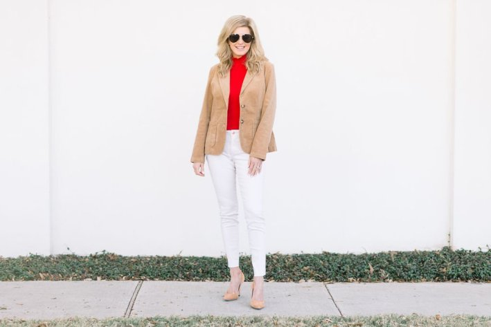 Tanya Foster standing on a sidewalk wearing red blouse, white jeans and jacket