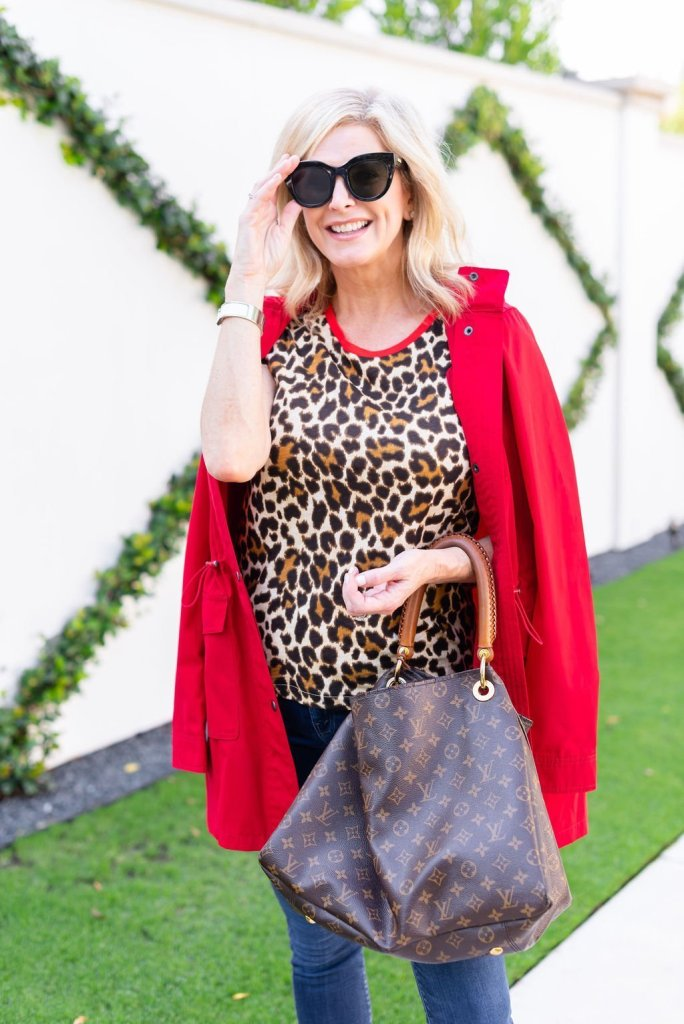 Talbots red raincoat | Introduction to my Fall Fashion Favorites by popular Dallas fashion blogger, Tanya Foster: image of a woman standing outside and wearing a red Talbots Hooded Anorak, leopard print tee, jeans, white sneakers, sunglasses, and holding a Louis Vuitton bag.