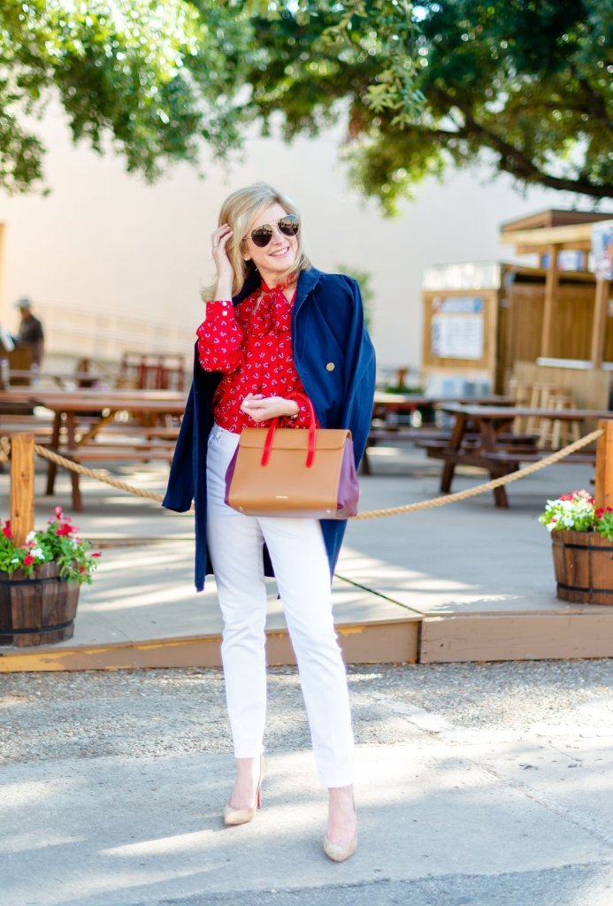 Fun at the State Fair of Texas with Draper James | Fun at The State Fair of Texas with Draper James by popular Dallas fashion blogger, Tanya Foster: image of a woman at the State Fair of Texas and wearing a Draper James Floral Tie Neck Blouse, Draper James Mid Rise Skinny Jean, Draper James Trench Coat and holding a Draper James Leather Satchel.