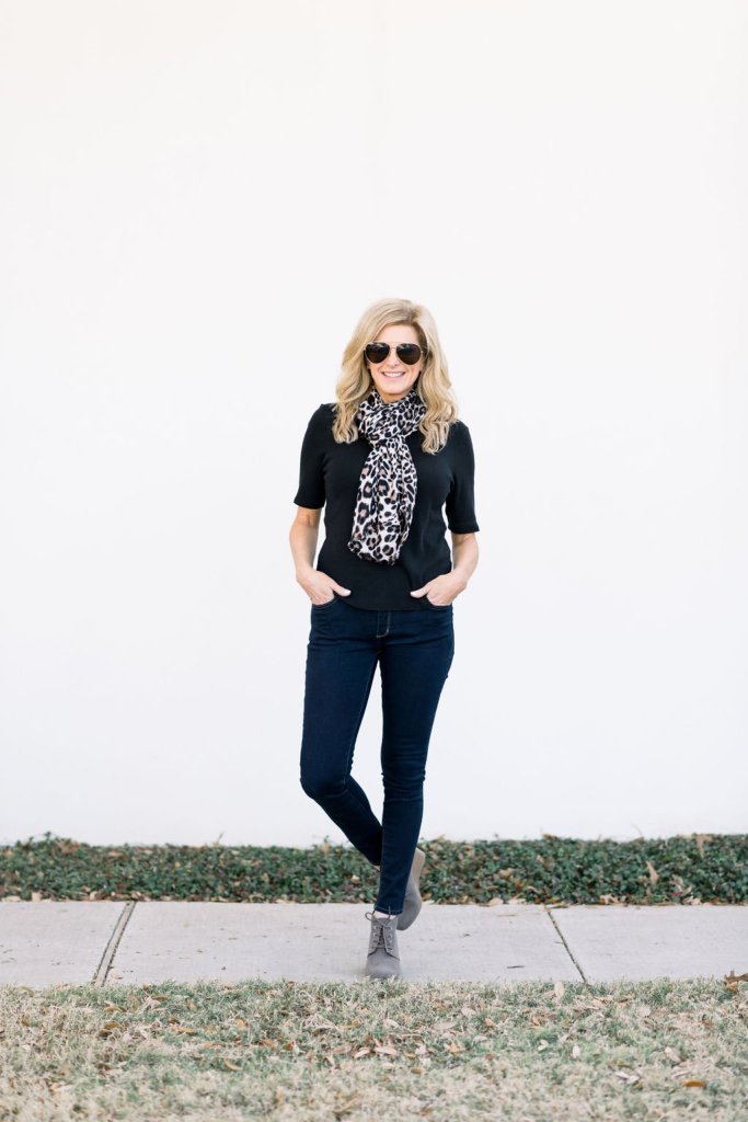 Tanya Foster standing on a sidewalk i booties, skinny jeans and black tee