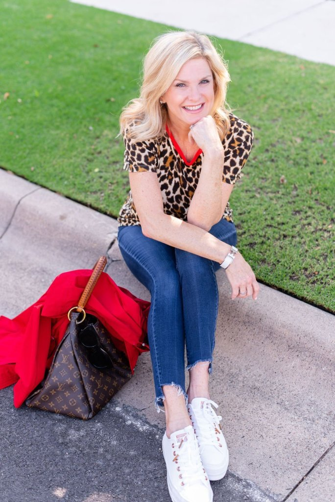 Talbots red raincoat | Introduction to my Fall Fashion Favorites by popular Dallas fashion blogger, Tanya Foster: image of a woman sitting outside on a street curb and wearing a red Talbots Hooded Anorak, leopard print tee, jeans, white sneakers, sunglasses, and holding a Louis Vuitton bag.