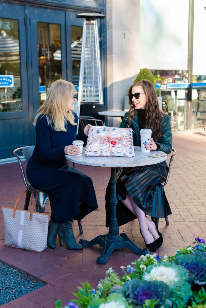 Tanya Foster and Laura Pearson sitting at a table having coffee while exchanging a gift