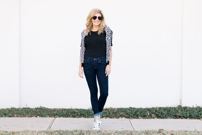 Tanya Foster standing on a sidewalk in animal print sweater, black tee and skinny jeans