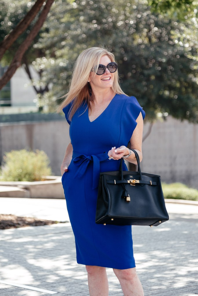 The Eliza J cobalt blue dress on the Nordstrom Anniversary Sale | 5 Best Designer Bags to Invest in and What's in my Bag by popular Dallas fashion blogger, Tanya Foster: image of a woman standing outside and holding a Hermes Birkin handbag.