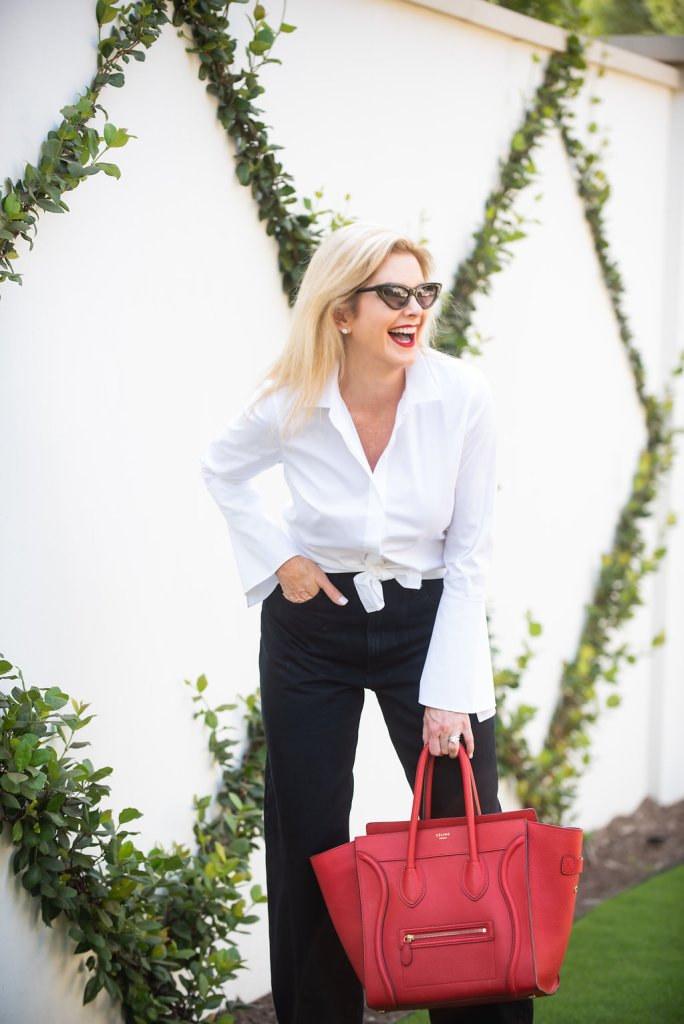 Lafayette 148 white blouse, black wide bottom jeans, red Celine bag, silver booties