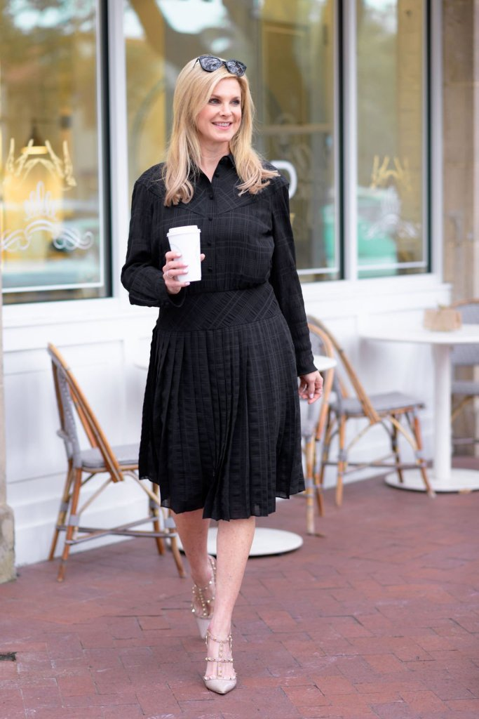 Tanya Foster walking and holding a coffee in a coach black dress, Valentino nude heels and coach sunglasses